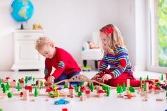 Kinder, die mit Spielzeugeisenbahn und -zug spielen Lizenzfreie Stockfotos