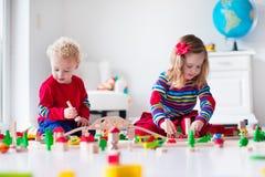 Kinder, die mit Spielzeugeisenbahn und -zug spielen Stockfoto