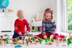 Kinder, die mit Spielzeugeisenbahn und -zug spielen Stockfotografie