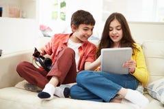 Kinder, die mit Tablet und MP3-Player spielen Stockbilder