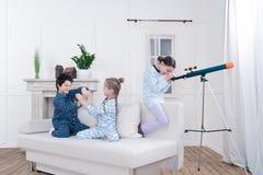 Kinder die mit teleskop spielen und heraus fenster schauen