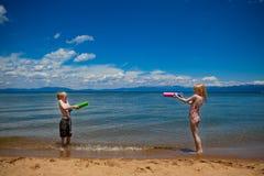 Kinder, die mit Wasser am Strand sich sprizen Lizenzfreie Stockfotografie
