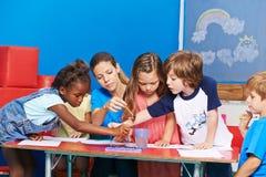 Kinder, die mit Wasserfarbe im Kindergarten malen Lizenzfreie Stockbilder