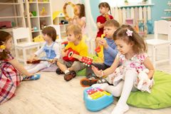 Kinder, die Musikinstrumente auf Lektion im Kindergarten lernen stockbilder