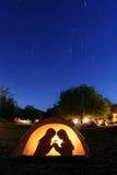 Kinder, die nachts in einem Zelt kampieren Stockbilder