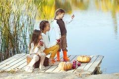Kinder, die nahe dem See im Herbst spielen Stockfoto
