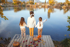 Kinder, die nahe dem See im Herbst spielen Stockbild
