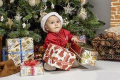 Kinder, die nahe dem Weihnachtsbaum mit Geschenken spielen Lizenzfreie Stockfotografie