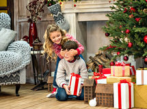 Kinder, die nahe Geschenkboxen sitzen Lizenzfreies Stockbild
