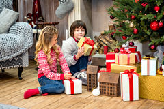 Kinder, die nahe Geschenkboxen sitzen Lizenzfreie Stockfotografie