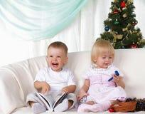 Kinder, die nahe zum Weihnachtenc$pelzbaum spielen Lizenzfreie Stockfotografie