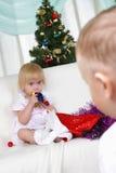 Kinder, die nahe zum Weihnachtenc$pelzbaum spielen Stockfotos