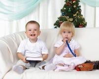 Kinder, die nahe zum Weihnachtenc$pelzbaum spielen Stockbilder