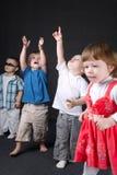 Kinder, die oben auf dunklen Hintergrund zeigen Stockbild