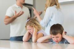 Kinder, die Ohren während Elternargumentierung bedecken stockfoto