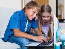 Kinder, die online auf Laptop spielen Stockfotos