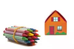 Kinder, die Papierhaus- und Wachszeichenstifte falten Lizenzfreie Stockfotos