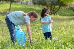 Kinder, die in Park s?ubern Freiwillige Kinder mit einer Abfalltasche, welche die S?nfte, Plastikflasche in die Wiederverwertung  stockfoto