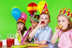 Kinder, die in Partyhupen durchbrennen Stockfoto