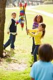 Kinder, die Pinata an der Geburtstagsfeier schlagen stockbild