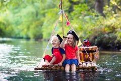 Kinder, die Piratenabenteuer auf hölzernem Floss spielen Lizenzfreies Stockfoto