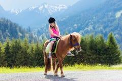 Kinder, die Pony reiten Kind auf Pferd in den Alpenbergen lizenzfreies stockbild