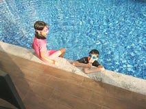 Kinder, die am Pool spielen lizenzfreies stockfoto