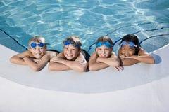 Kinder, die am Rand des Swimmingpools lächeln Stockfotografie