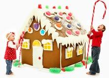 Kinder, die riesigen Weihnachtslebkuchen Hous aufbauen lizenzfreies stockfoto