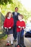 Kinder, die Roller auf ihren Schulweg mit Vater reiten lizenzfreies stockbild