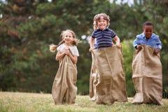 Kinder, die am Sackrennen konkurrieren Lizenzfreies Stockfoto