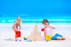 Kinder, die Sandburg auf dem Strand errichten Stockfotos