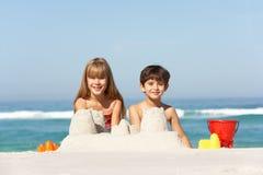 Kinder, die Sandcastles am Strand-Feiertag aufbauen Stockfotos