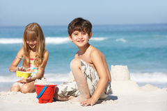 Kinder, die Sandcastles am Strand-Feiertag aufbauen Lizenzfreie Stockfotos