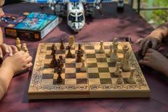 Kinder, die Schach im Garten mit unscharfen Spielwaren auf Hintergrund spielen stockfoto