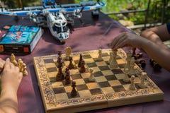 Kinder, die Schach im Garten mit unscharfen Spielwaren auf Hintergrund spielen lizenzfreie stockbilder