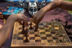 Kinder, die Schach im Garten mit unscharfen Spielwaren auf Hintergrund spielen stockfotos