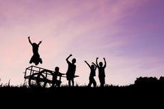 Kinder, die Schattenbild auf Farbe des Himmels spielen Lizenzfreie Stockbilder