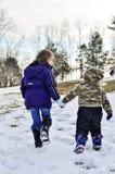 Kinder, die in Schneehändchenhalten gehen stockbild