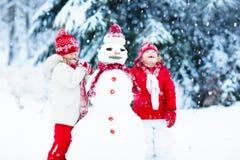 Kinder, die Schneemann errichten Kinder im Schnee Antreiben in einen Schlitten lizenzfreie stockbilder