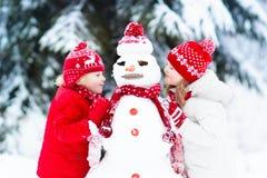 Kinder, die Schneemann errichten Kinder im Schnee Antreiben in einen Schlitten Stockfotografie