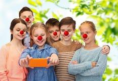 Kinder, die selfie mit Smartphone am roten Nasentag nehmen lizenzfreie stockbilder