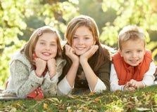 Kinder, die sich draußen in der Herbst-Landschaft entspannen Lizenzfreies Stockbild