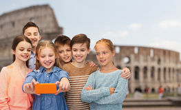 Kinder, die Smartphone selfie über Kolosseum sprechen Lizenzfreie Stockfotografie