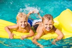 Kinder, die Sommer-Tag am Pool genießen Stockfotografie