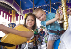 Kinder, die Spaß auf einem Karneval Karussell haben Lizenzfreie Stockfotos