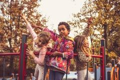 Kinder, die Spaß auf Spielplatz haben stockbild