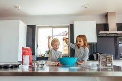 Kinder, die Spaß bei der Herstellung des Kuchenteiges haben lizenzfreie stockfotografie