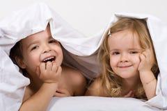 Kinder, die Spaß im Bett haben stockfotos