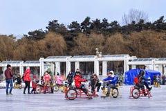 Kinder, die Spaß mit dem Sledging auf Eis in Nanhu-Park, Changchun, China haben Lizenzfreie Stockfotografie